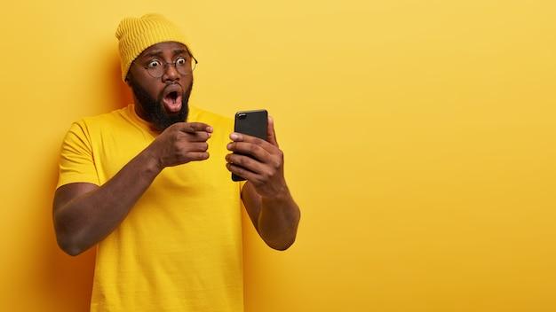 Nerveuze knappe man met bril poseren met zijn telefoon