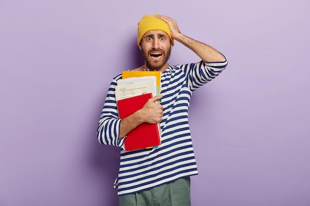 Nerveuze man die in paniek is, hand op het hoofd houdt, kijkt met beschaamde gezichtsuitdrukking, houdt de mond open, draagt notitieblok met papieren