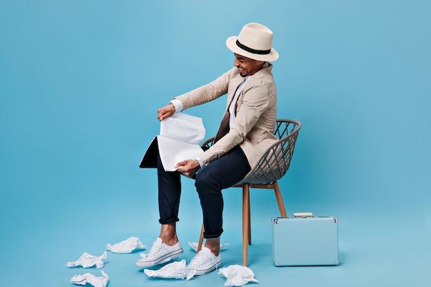Nerveuze man in beige outfit die bladen van boek scheurt
