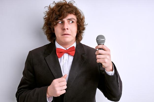 Nerveuze man is bang voor openbare toespraak en zweten geïsoleerd op een witte achtergrond, met microfoon in handen