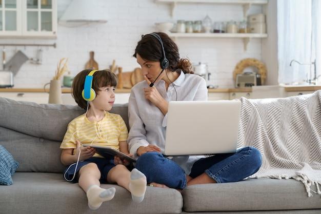 Nerveuze moeder zittend op de bank thuis tijdens lockdown werk op laptop kind leidt af van het werk