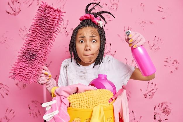 Nerveuze slordige huisvrouw drukt op lippen brengt huis op orde maakt kamer schoon houdt dweil vast en schoonmaakmiddel wil geen vuil appartement verzamelt vuile was geïsoleerd over roze muur