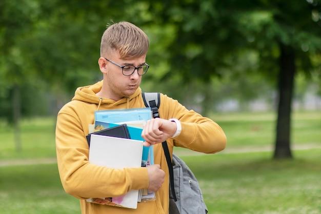 Nerveuze universiteitsstudent in glazen met rugzak en boeken haast zich naar les, tijd op polshorloges controleren