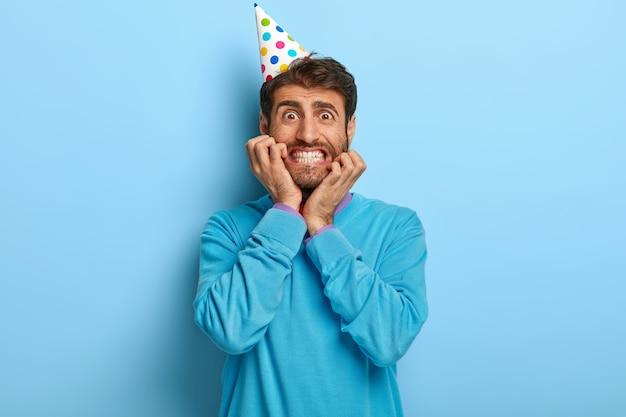 Nerveuze verbaasde man met verjaardagshoed poseren in blauwe trui