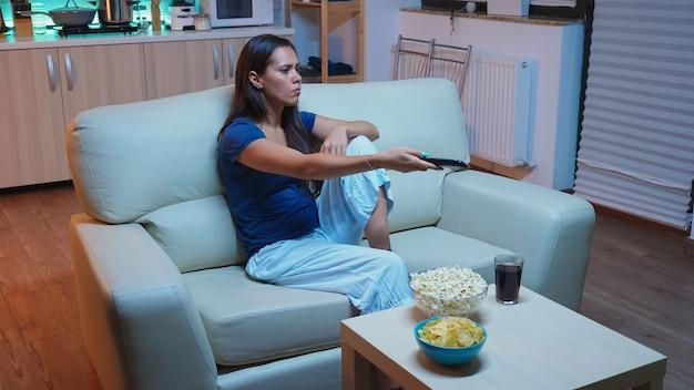 Nerveuze vrouw met televisie-afstandsbediening zittend op de bank. verveelde, boze eenzame dame die ontspant terwijl ze tv kijkt, liggend op een comfortabele bank met de controller die een film zoekt die de kanalen verandert.