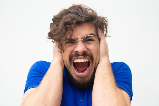 Nerveuze wanhopige man die oren bedekt met handen