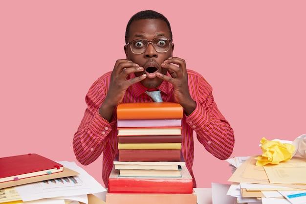 Nerveuze zwarte student kijkt verbaasd, houdt handen bij de mond, bang om iets te lezen, gekleed in formele kleding