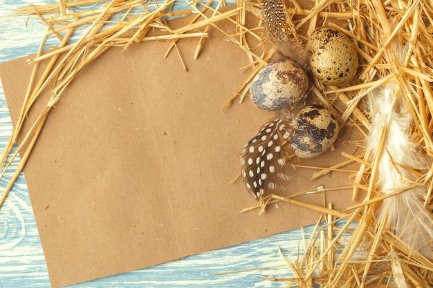 Nest met paaseieren op blauwe houten oppervlak, bovenaanzicht met kopie ruimte