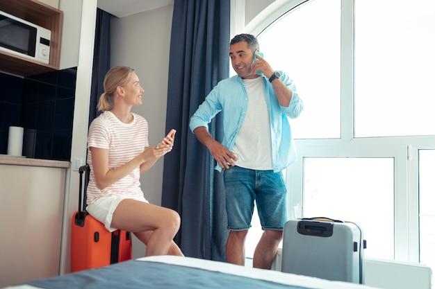 Net aangekomen. gelukkig getrouwd stel zit in hun hotelkamer en belt hun familieleden om hun indrukken te delen.