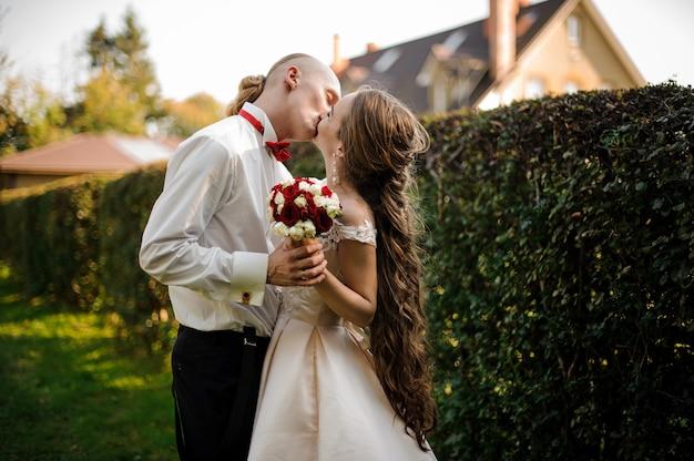 Net getrouwd gelukkige man en vrouw die elkaar kussen in het groene park. conceptie van de bruiloft