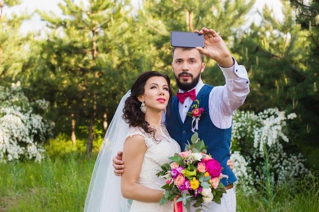 Net getrouwd stel selfie maken in het park