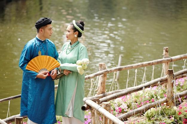 Net getrouwde vietnamese man en vrouw in traditionele jurken die op een houten brug staan en naar elkaar glimlachen