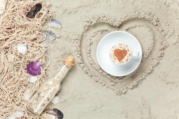 Net, schelpen met fles en geschenkdoos met hartvorm op zand.