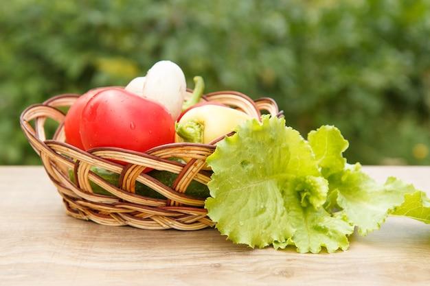 Net tomaten en gele paprika geplukt in een rieten mand met slablaadjes op houten planken. net geoogste groenten