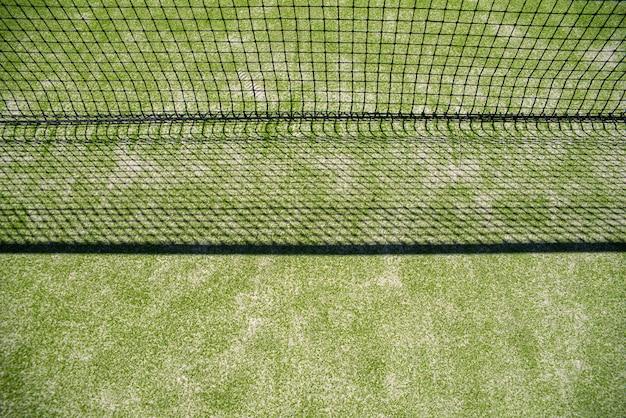 Net van een tennisbaan die zijn schaduw op het gras projecteert