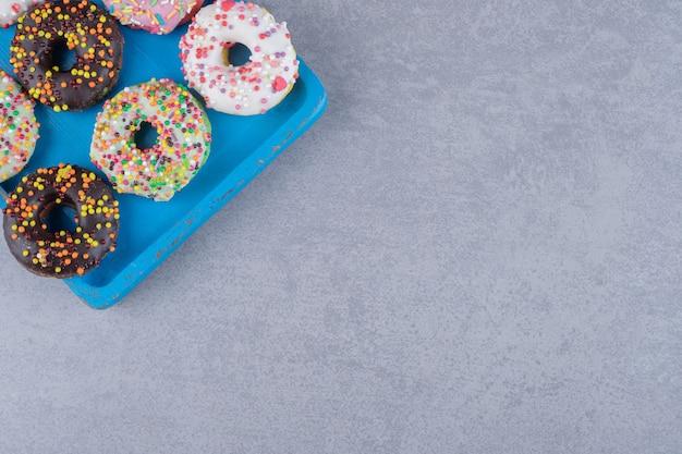 Netjes gerangschikte donuts op een schaal op een marmeren ondergrond