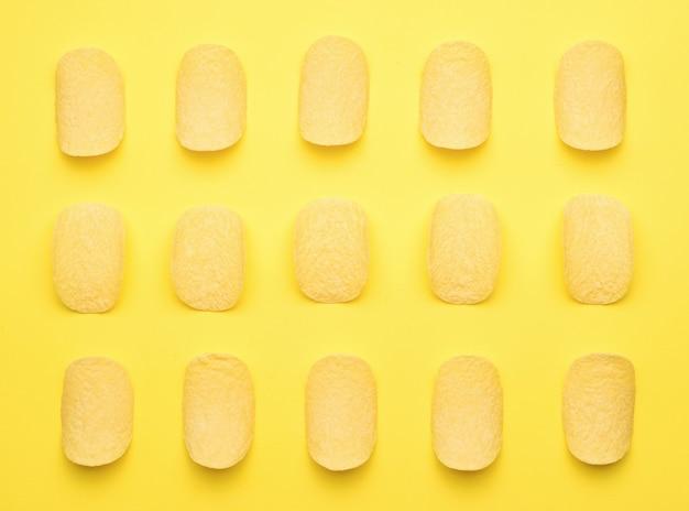 Netjes gestapelde chips op een gele achtergrond. een populair aardappelgerecht. plat leggen.