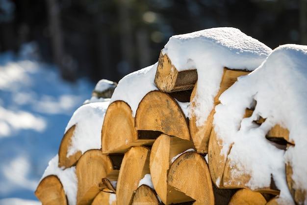 Netjes opgestapelde stapel gehakte droge stammen hout bedekt met sneeuw buiten op heldere koude zonnige winterdag, abstracte achtergrond, brandhout logboeken voorbereid voor de winter, klaar om te branden.