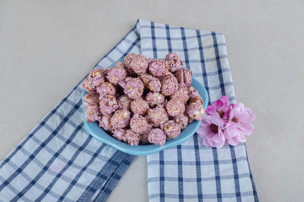 Netjes opgevouwen handdoek onder een schaal met popcornsnoepjes en bloemenkroon op marmeren tafel.