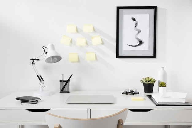 Nette en overzichtelijke werkruimte met lamp op het bureau