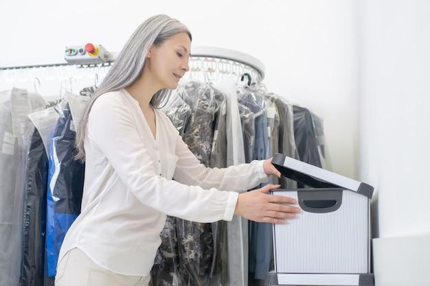 Nette glimlachende vrouw die zich in profielcontainer met orde dichtbij klerenrek in chemisch reinigen bevindt sluit