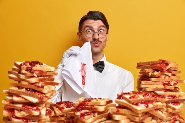 Nette ober in uniform en witte handschoenen, veegt mond af met servet, werkt in restaurant, staat aan tafel overladen met jam toast,