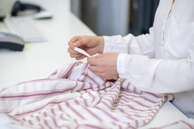 Nette vrouwelijke handen aanraken van label van gestreepte kleding liggend op de toonbank, geen gezicht
