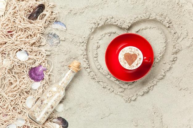 Netto, schelpen met fles en geschenkdoos met kop hartvorm op zand achtergrond.