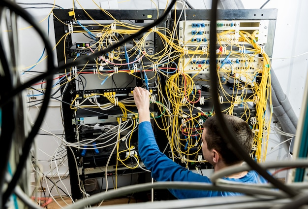 Netwerkingenieur die in serverruimte werkt. netwerkkabels aansluiten op switches
