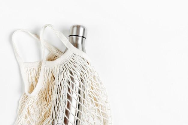 Netzakken met herbruikbare metalen waterfles op witte achtergrond. duurzame levensstijl.