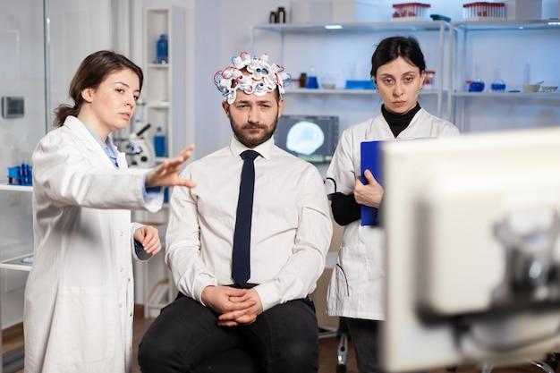Neurologische onderzoekers die het resultaat van de behandeling uitleggen, wijzend op de monitor terwijl de medische wetenschapper aantekeningen maakt, de headset scant die zich voorbereidt op de hersenscan die elektrische activiteit analyseert.