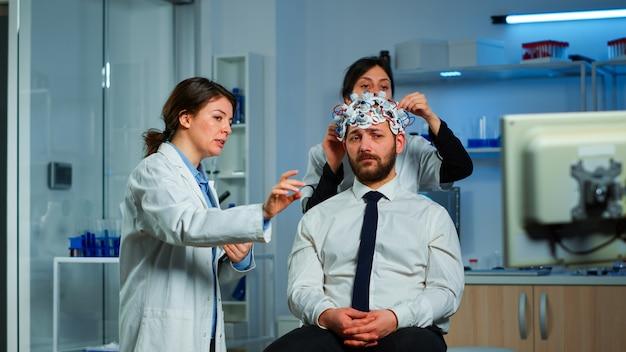Neurologische onderzoekers die het resultaat van de behandeling uitleggen, wijzend op de monitor terwijl de medische wetenschapper de headset voor het scannen van hersengolven aanpast en zich voorbereidt op de hersenscan die elektrische activiteit analyseert