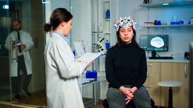 Neuroloog arts die symptomen vraagt van de patiënt die aantekeningen maakt op het klembord, high-tech hersenscanner aanpast