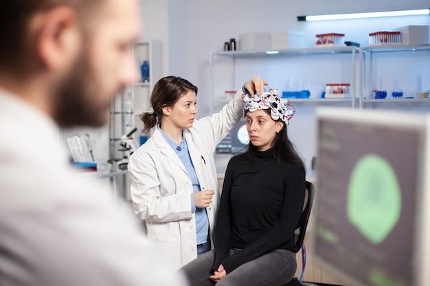 Neuroloog arts in geneeskunde lab headset met sensoren, moderne faciliteit voor wetenschap aan te passen. patiënt met hersenscan, high-tech tomografie-informatie.