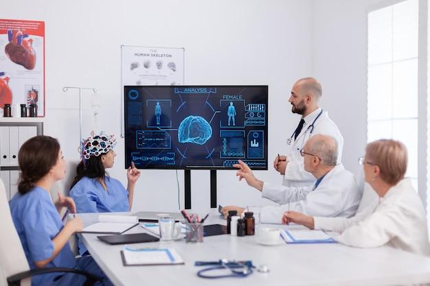 Neuroloog man arts die hersenexpertise controleert met behulp van een headset met sensoren op een vrouwelijke assistent in de vergaderruimte van het ziekenhuis. artsenteam dat ziektebehandeling analyseert en medische radiografie onderzoekt