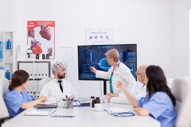 Neuroloog senior vrouwelijke arts die medische expertise van de hersenen presenteert tijdens de gezondheidszorgconferentie