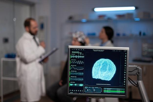 Neurowetenschappelijke arts met klembord die behandeling tegen hersenziekte toont aan patiënt met eeg-headset. vrouw zit in neurologisch wetenschappelijk laboratorium dat disfuncties van het zenuwstelsel behandelt.