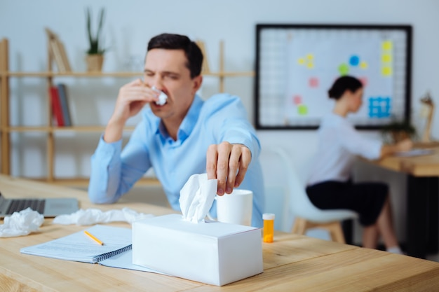 Neus afvegen. silhouet van zieke kantoormedewerker die op zijn werkplek zit en opzij kijkt