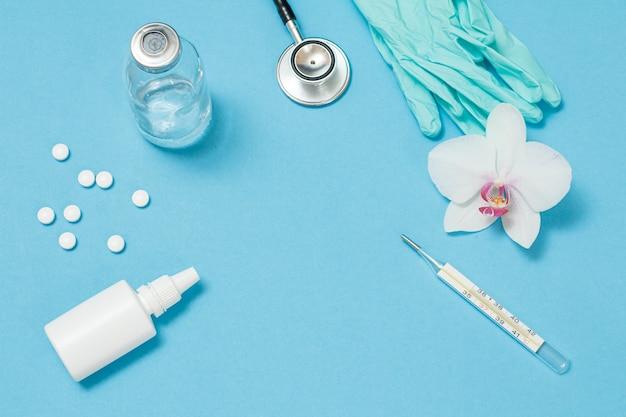 Neusspray, pillen, een glazen kwikthermometer, een phonendoscope en nitrilhandschoenen voor persoonlijke bescherming