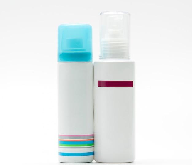 Nevelfles met blauwe glb en pompfles huidverzorging op witte achtergrond, leeg etiket
