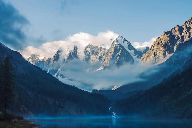 Nevelig landschap met bergmeer en mist boven water