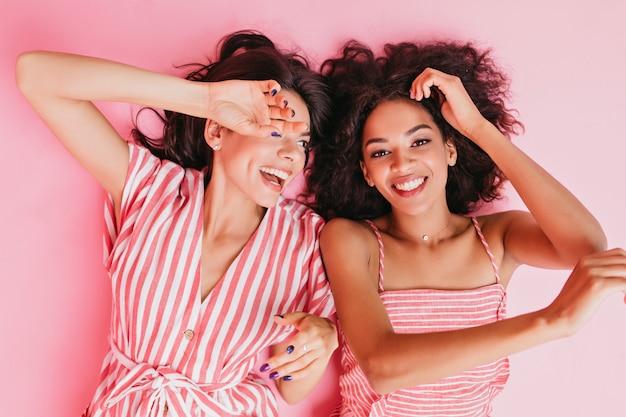 Neven in een geweldige bui liggen opgewekt op de grond. meisjes poseren met een oprechte glimlach in roze kleding voor close-upportretten.