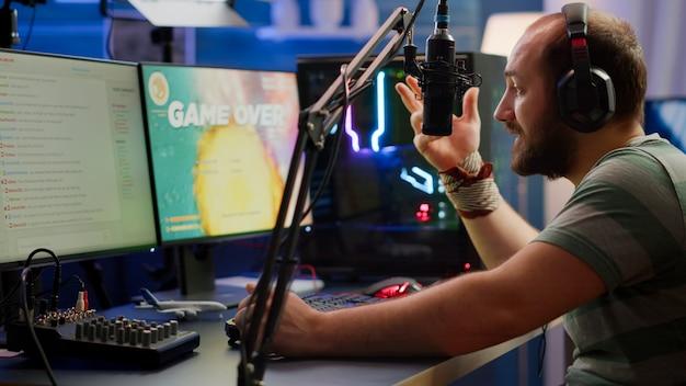 Nevous-streamer verliest videogame, game over voor man cyber die online space shooter-games speelt met headset. speler die presteert op een krachtige computer en praat met spelers tijdens de chat in gamecompetitie