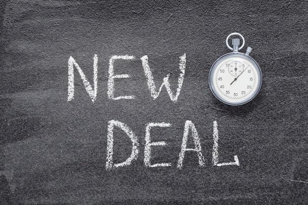 New deal zin geschreven op schoolbord met vintage nauwkeurige stopwatch