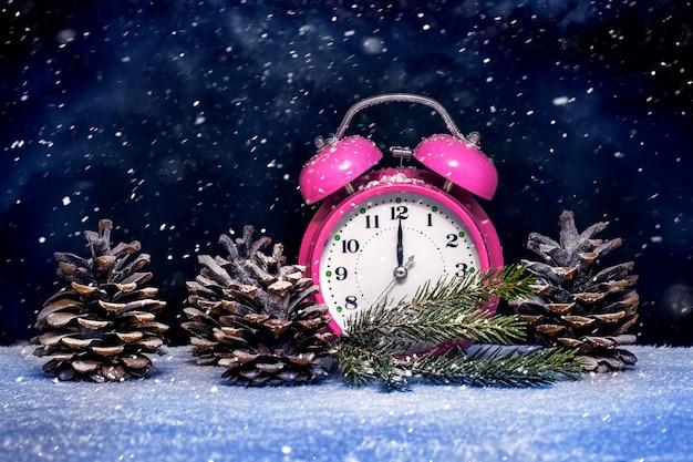 New year's wenskaart met een klok en kegels tijdens de sneeuwval op oudejaarsavond