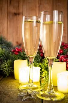 New years kerstviering achtergrond. twee glazen met champagne op houten achtergrond van kerstdecor en kerstballen kopiëren ruimte