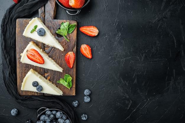 New york cheesecake of klassieke cheesecake met verse bessen, op zwart