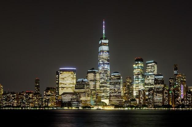 New york city manhattan ny skyline panorama 's nachts over de hudson rivier met reflecties vanuit new jersey usa