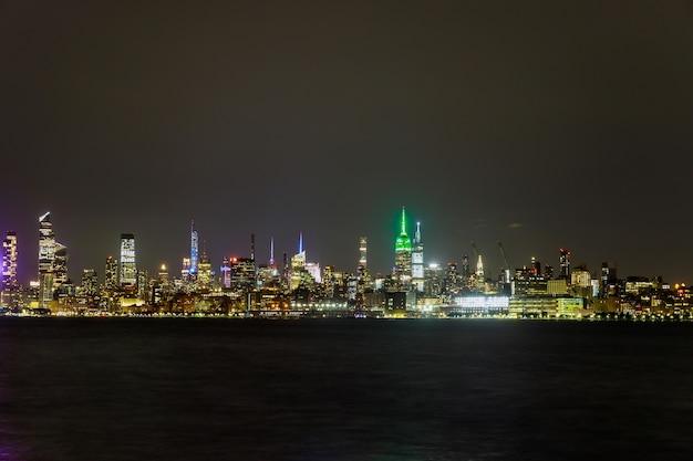 New york city panorama skyline bij manhattan kantoorgebouwen 's nachts ny usa