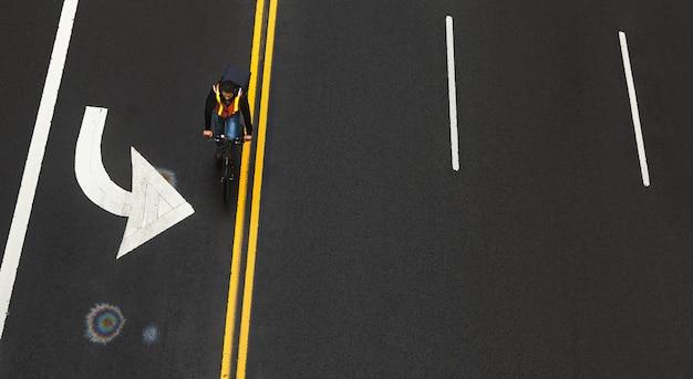 New york, verenigde staten - 03 mei 2016: wegmarkeringen op asfalt op straat van manhattan in new york city. beweging blured fietser beweegt langs de weg. iriserende vlek van benzine op asfalt